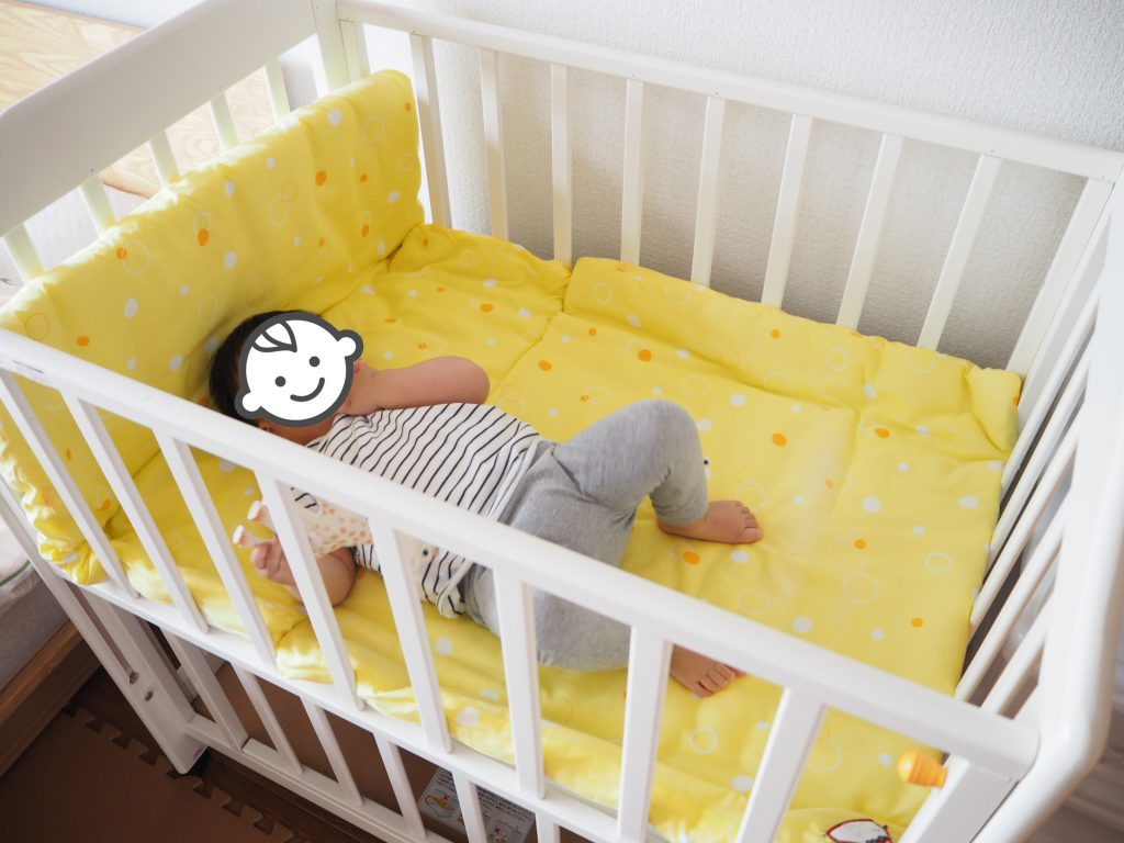 ミニベビーベッドに寝そべる赤子